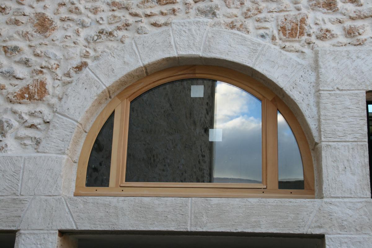 Fenêtre demi-lune en bois avec encadrements en fausses pierres